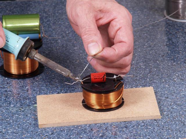 Über die zweite Spule wird der kleine Kondensator gelötet. Das vorherige Beinewickeln ist auch hier angebracht